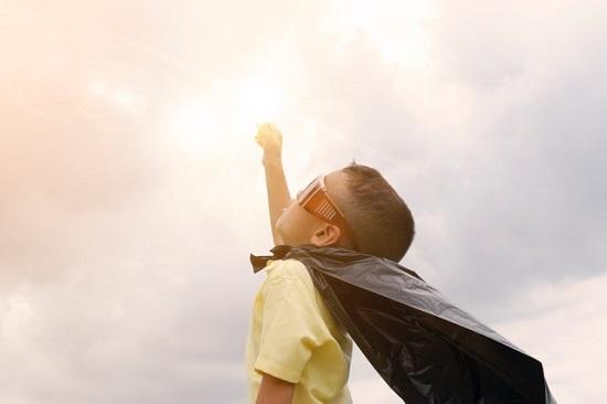 ילד עם גלימה עושה כמו סופרמן